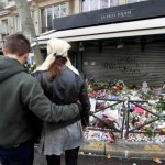A couple share a quiet moment in front of flowers, candles and messages in tribute to victims in front of the La Belle Equipe cafe, one of the sites of the deadly attacks in Paris