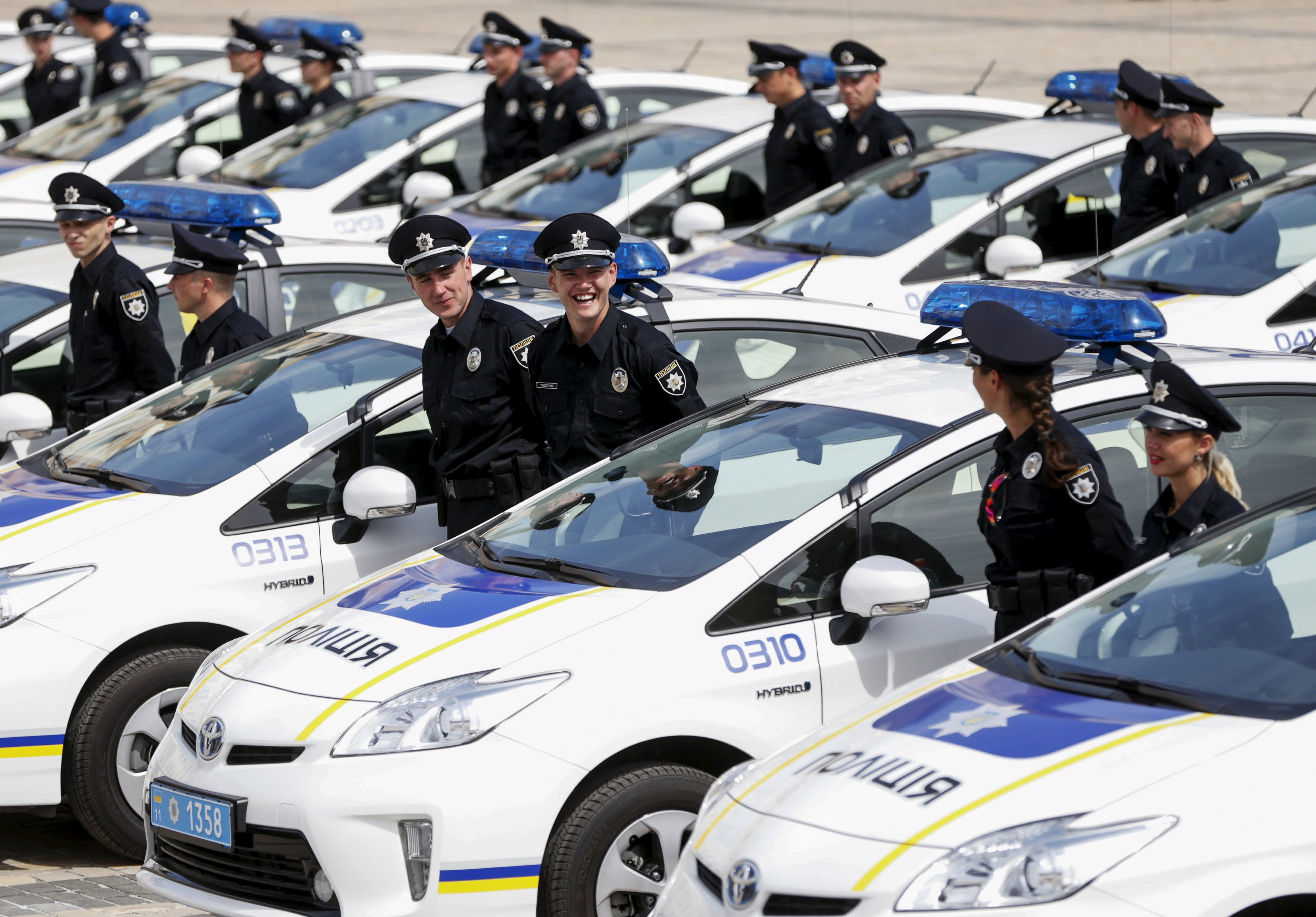 Police officers stand amidst cars before an oath-taking ceremony, which started up the work of a new police patrol service, in Kiev