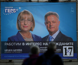 People walk near election poster of the presidential candidate of the Bulgaria's ruling centre-right GERB party, Tsacheva in Plovdiv